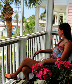 a lady relaxing on the private balcony of Lucky Catch condo